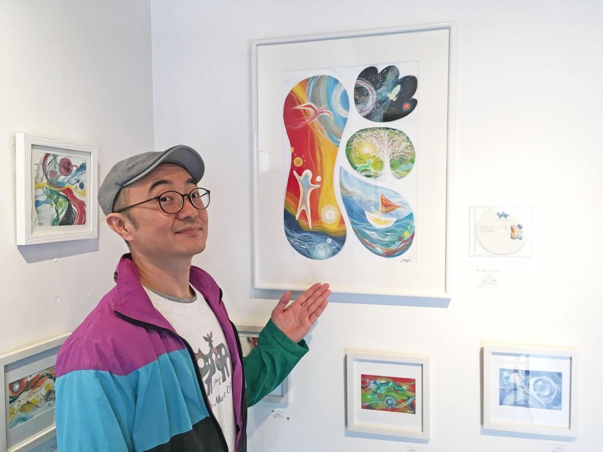 画家のShirasuさん。作品展のタイトルにもなった作品「君と冒険のはじまり」と共に