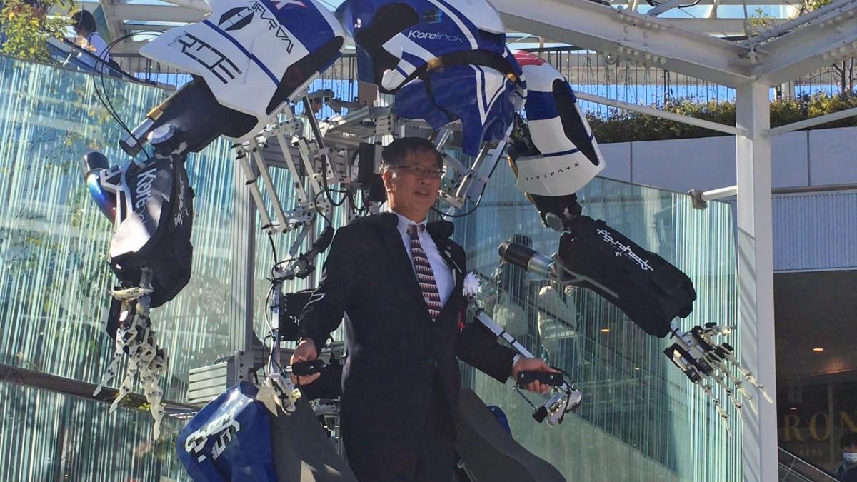 パワードスーツ型のエンターテインメントロボット、スケルトニクスに試乗する鈴木恒夫藤沢市長