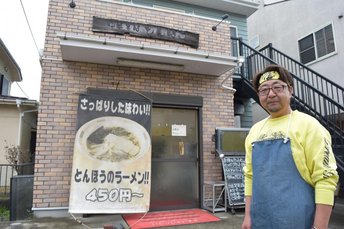 「中華そばとんほう」を背に立つ2代目の吉澤年也さん