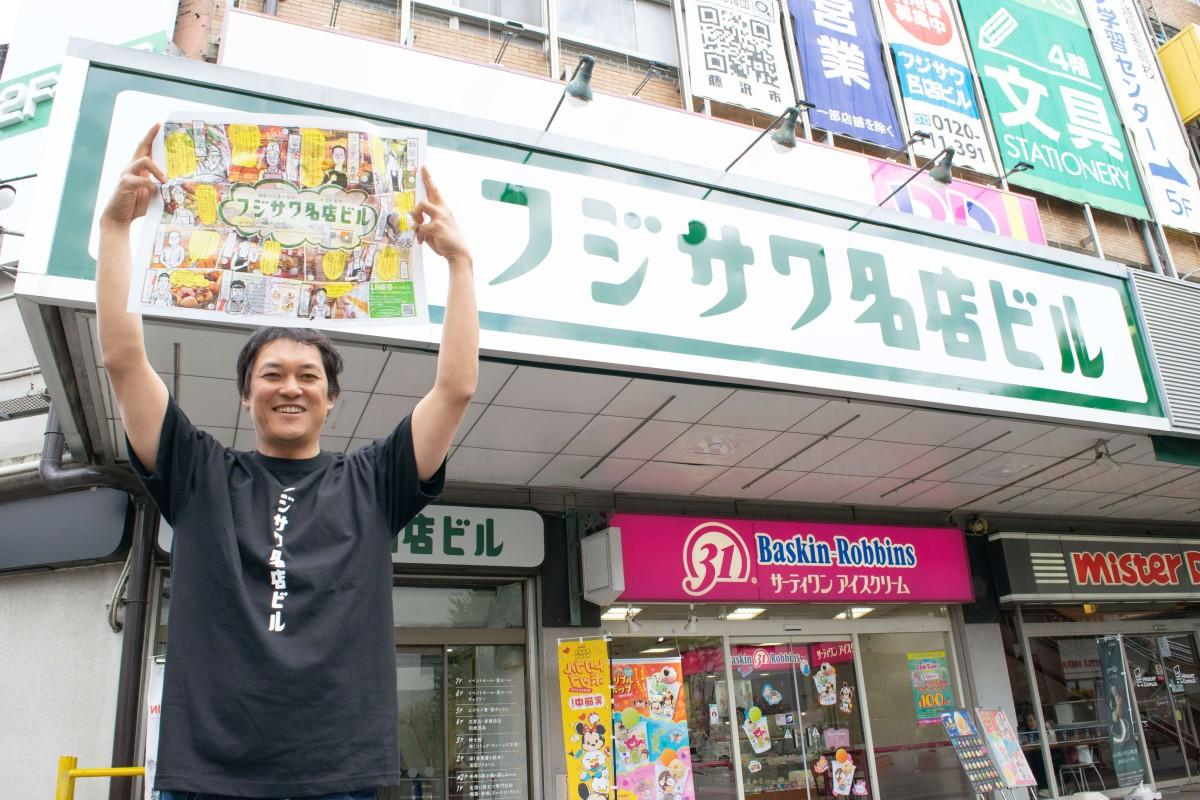新たなロゴの名店ビルを背に、出来上がったチラシを掲げる増田隆一郎さん