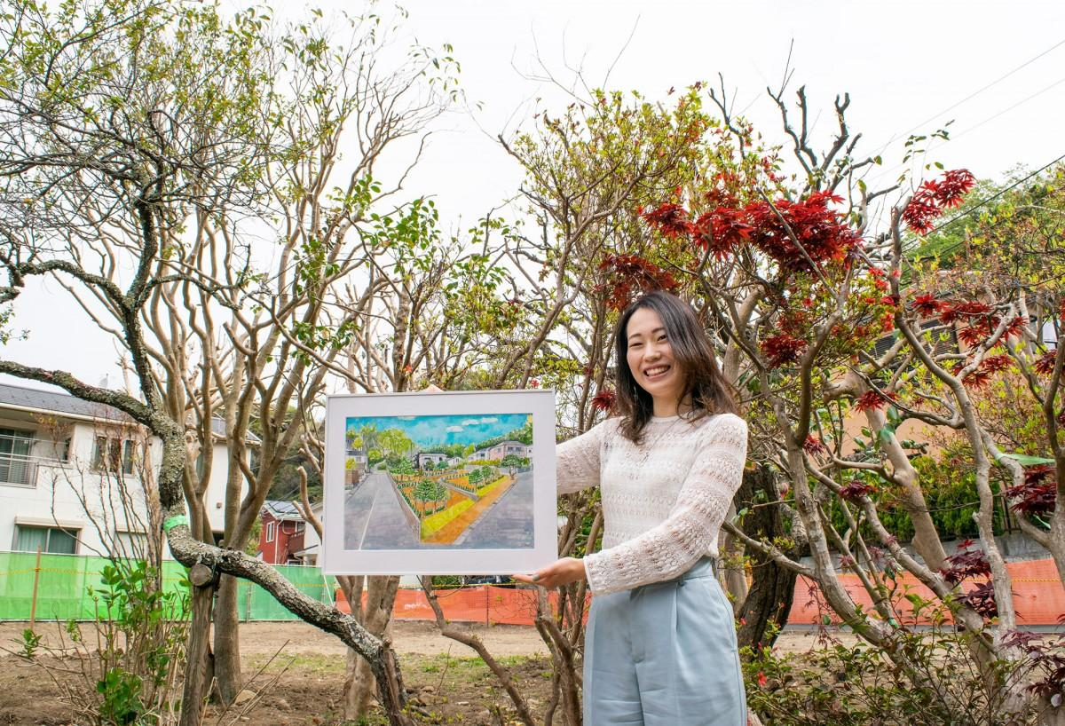 仕上がりイメージ図(一級建築士の谷真美さん作画)を抱き微笑む広報担当の貞松さん