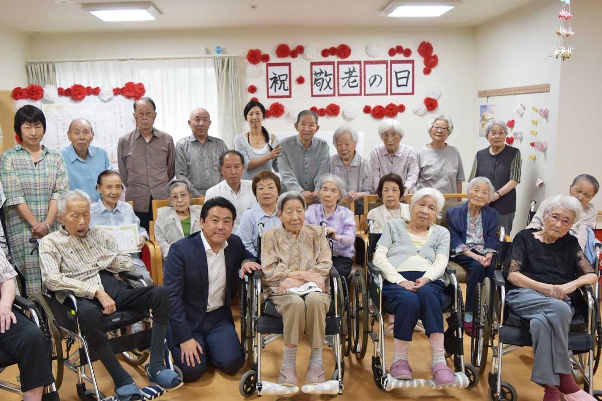 100歳を迎えた原田コウさん(最前列中央)と同施設利用者