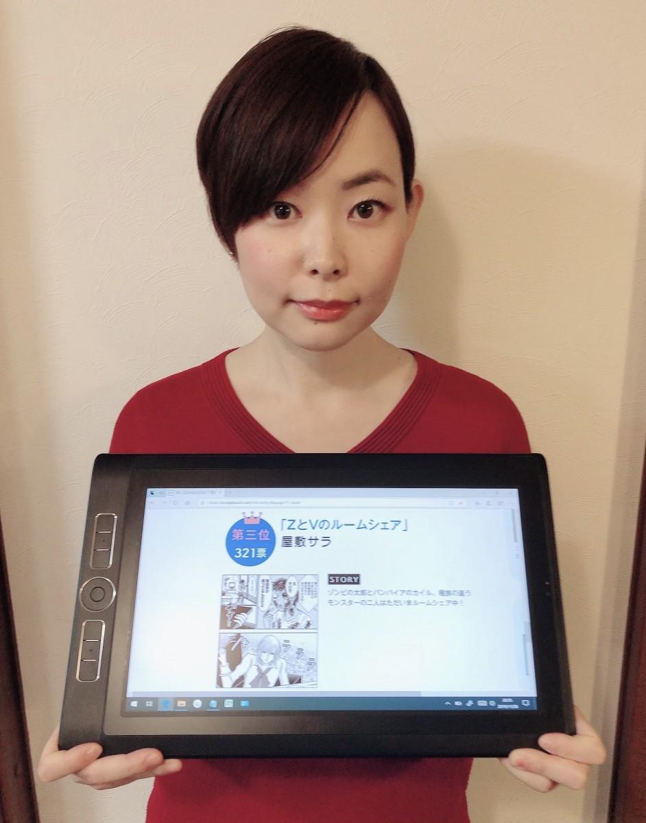 3位入賞作品「ZとVのルームシェア」が映るタブレットを持つ屋敷サラさん