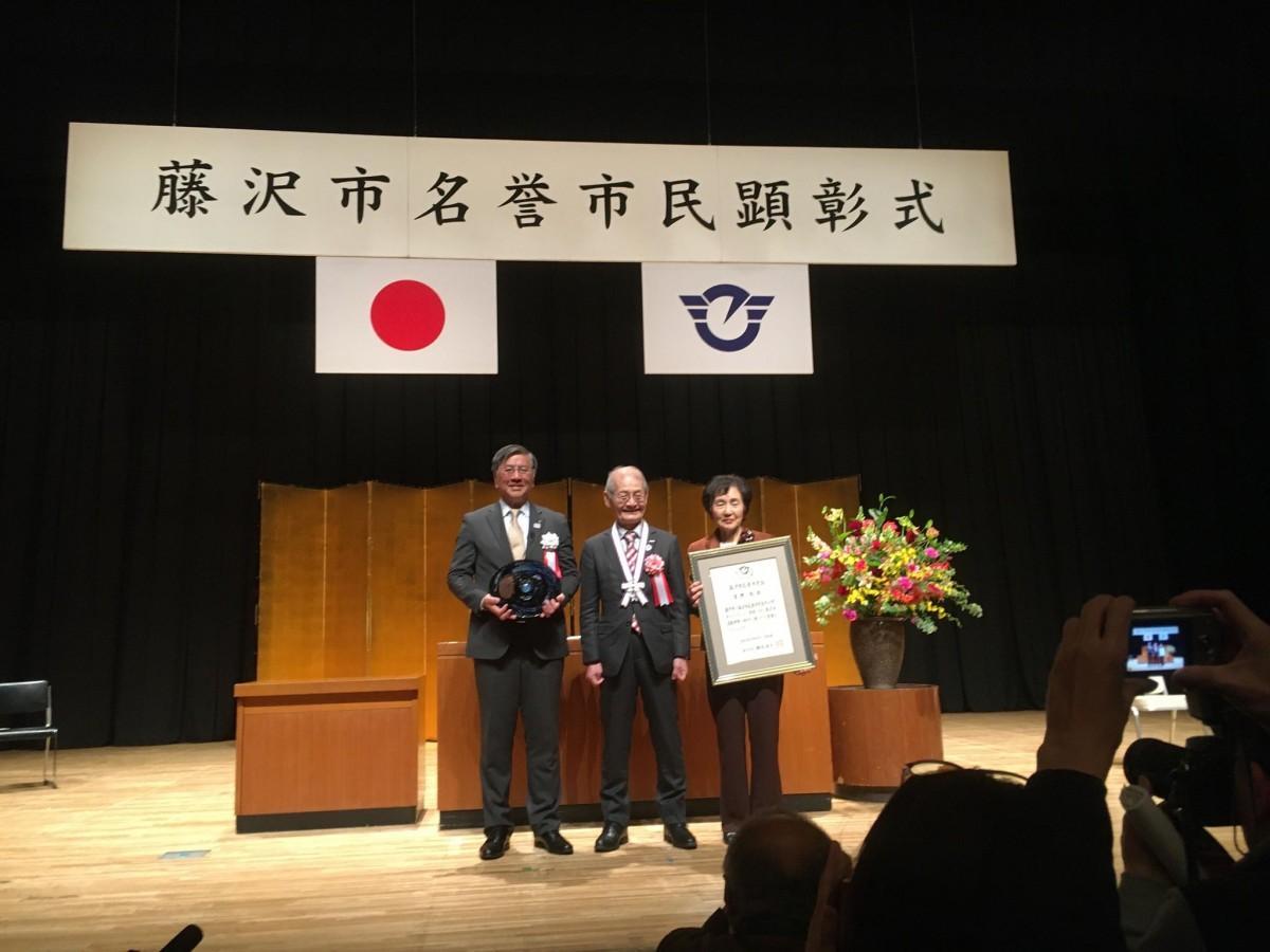 市民顕彰を受け、写真撮影に応じる吉野彰さん(中央)と妻の久美子さん(右)。写真左は鈴木恒夫藤沢市長。
