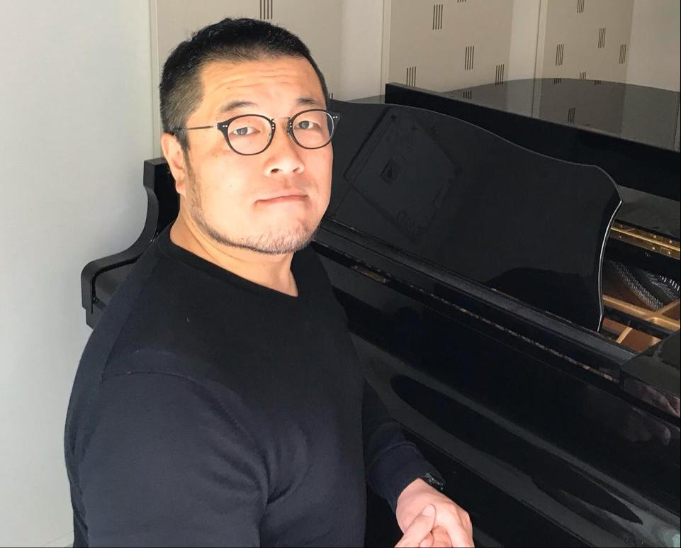 自宅のピアノ前に座る、発起人の高木敏郎さん