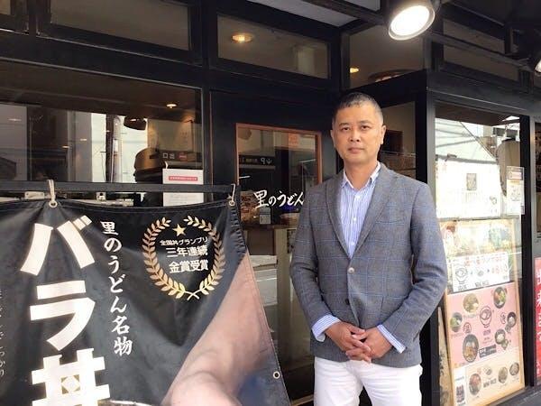 「里のうどん」の店舗前に立つ西嶋芳生社長