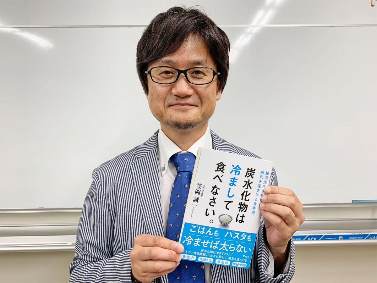 著書を掲げる、文教大学教授の笠岡誠一さん