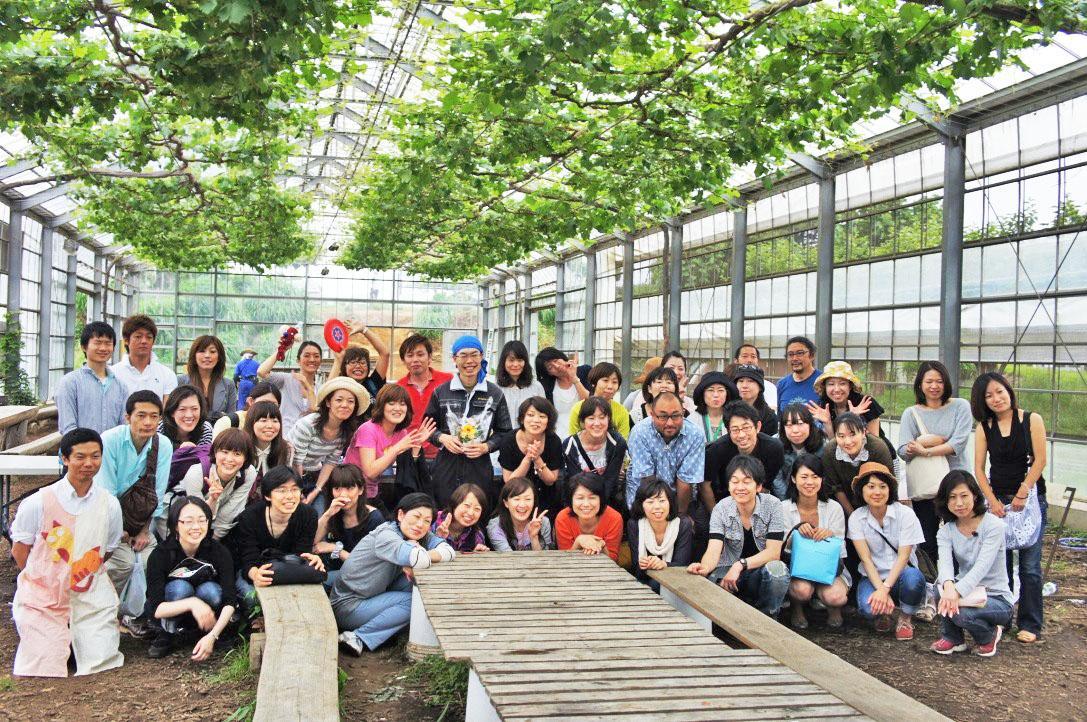 みやじ豚バーベキューの会場で参加者と集合写真を撮る宮治勇輔社長(中央)*写真は2019年以前に撮影したもの