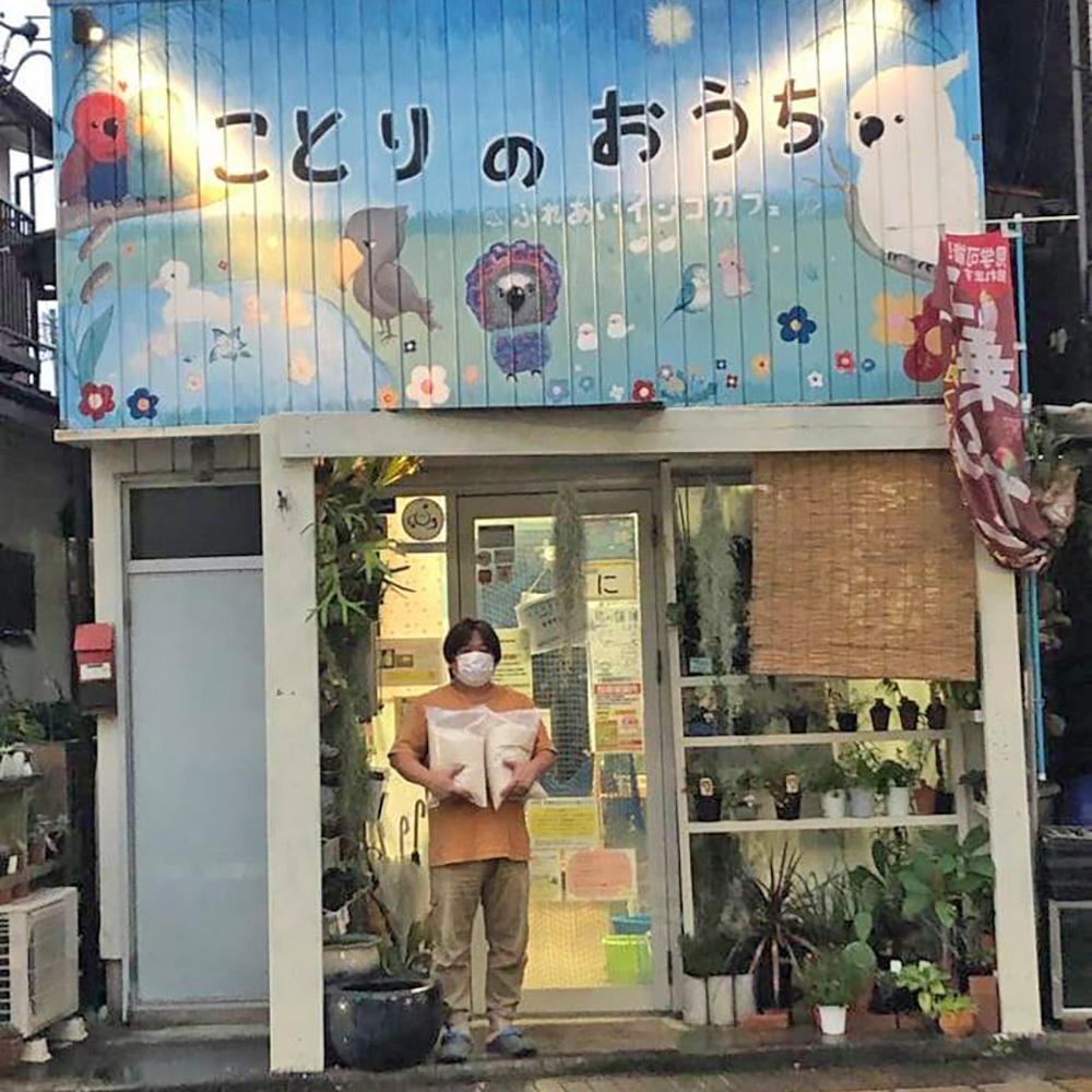 「ことりのおうち~ふれあいインコカフェ」の前で、ゼンショーホールディングスから提供されたお米を抱える、長後こども食堂代表の髙見広海さん