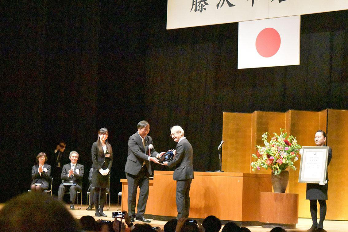 名誉市民顕彰授賞式で、鈴木恒夫藤沢市長から記念品を受け取る笑顔の ...