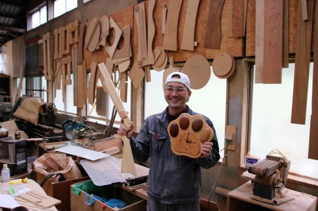 木工作品を持つ小松さん