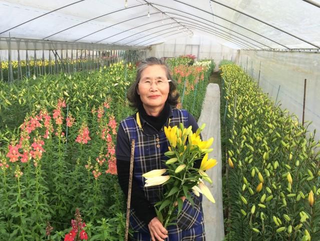 ビニールハウスで花を持つ藤田さん