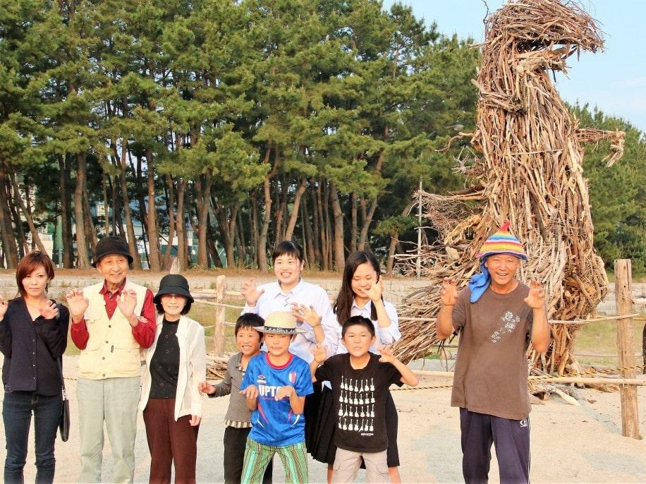 流木ゴジラの最後の様子を観覧者と共に記念撮影する重山さん(右)