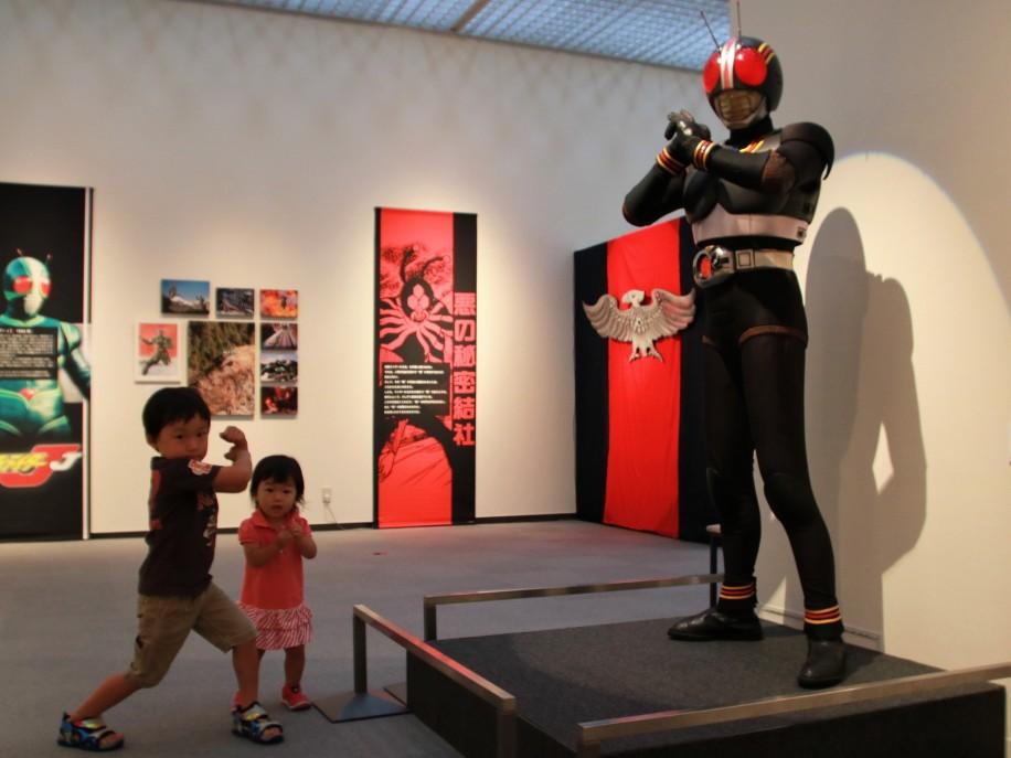 仮面ライダー「BLACK」の前で変身ポーズを決めるきょうだい