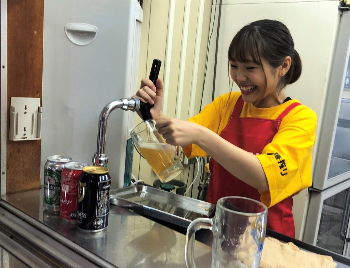 ジョッキにビールを注ぐ女性スタッフ