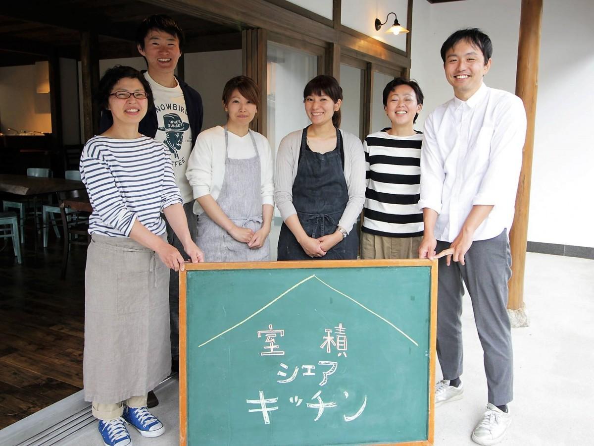 「@カフェ」のスタッフらに囲まれ微笑む店主の石本さん(中央)