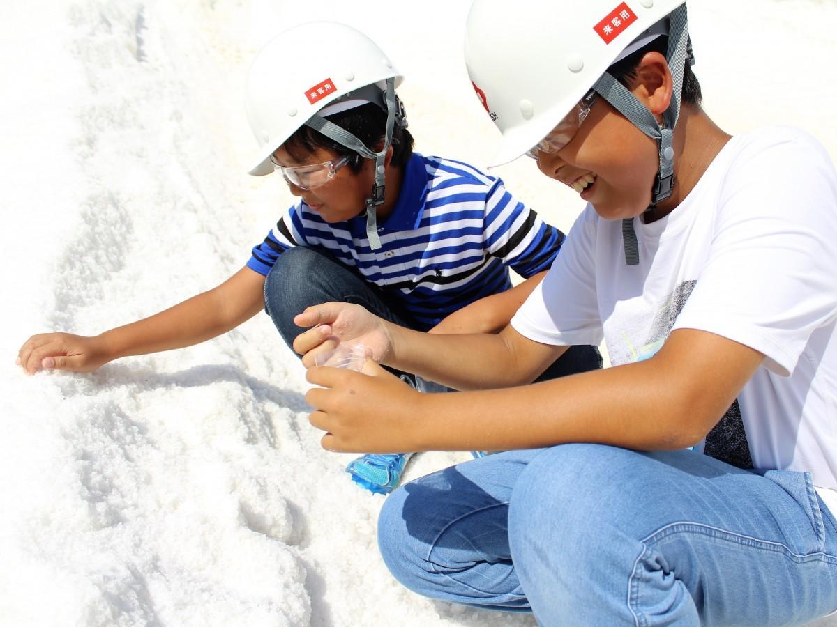 塩山で、塩を採取する児童ら