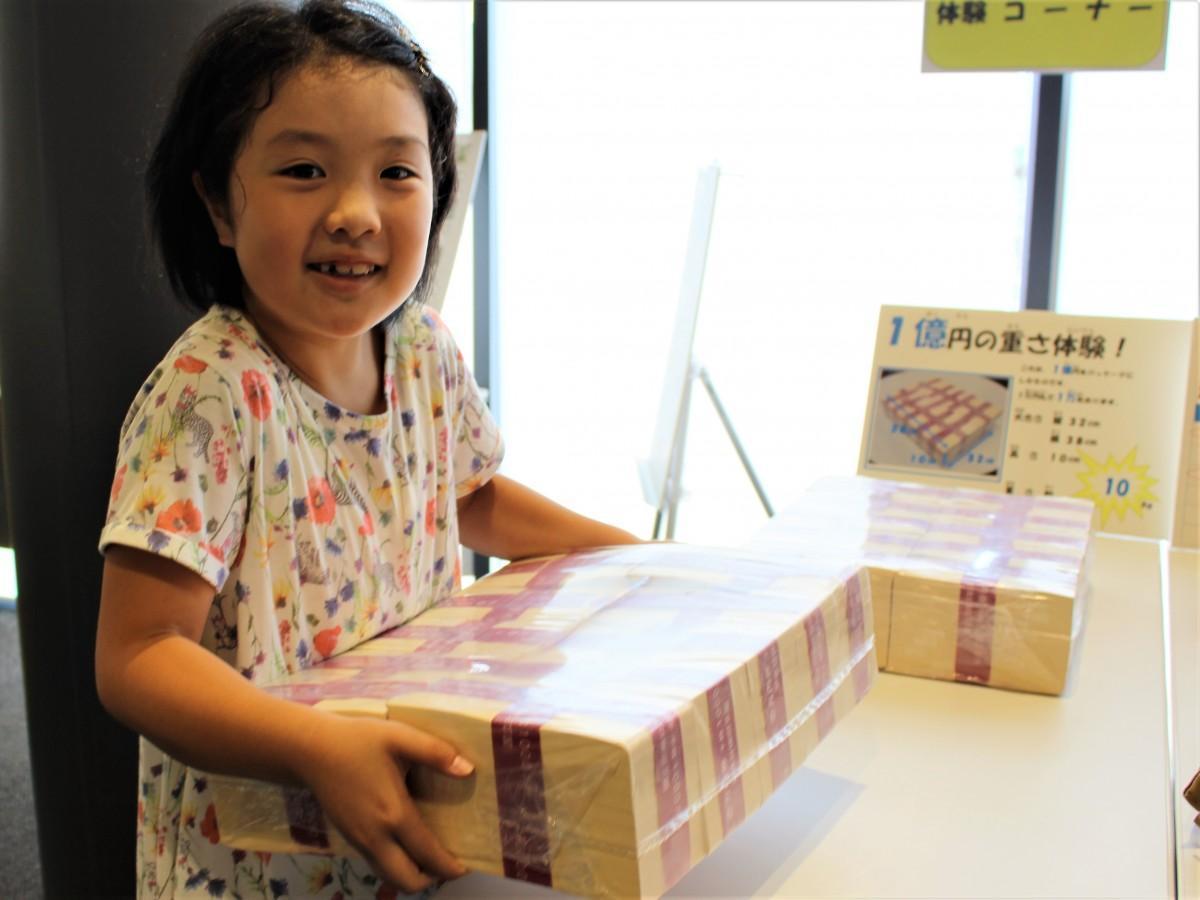 1億円(模擬券)の重さ体験する児童