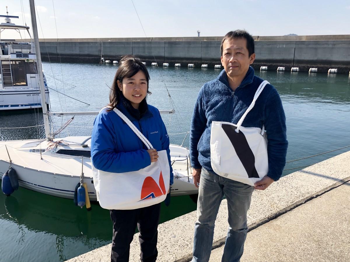 ヨットセイルを再利用したトートバッグを持つ中村さん(右)