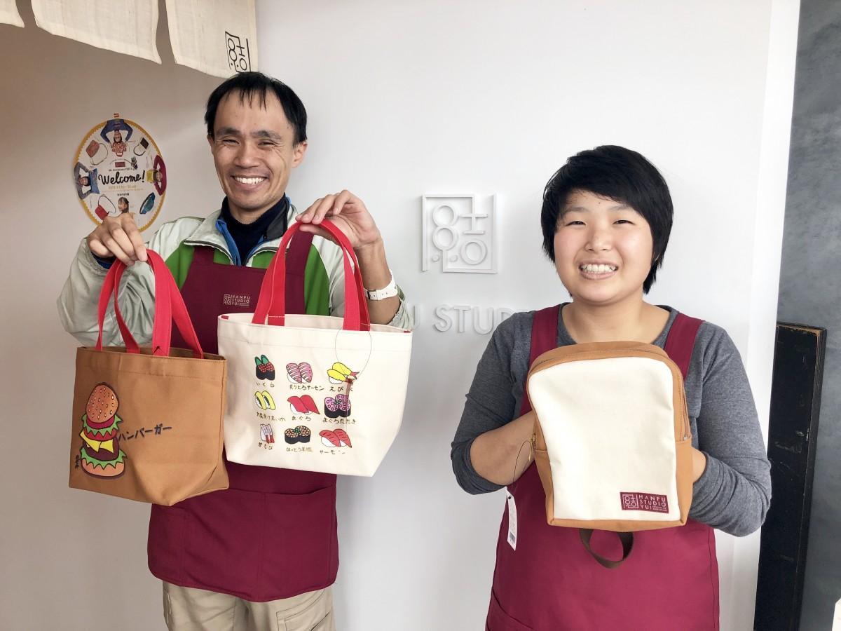 新作バッグを持つ手縫い担当の久米文子さん(右)と販売担当の野嵜裕太さん(左)