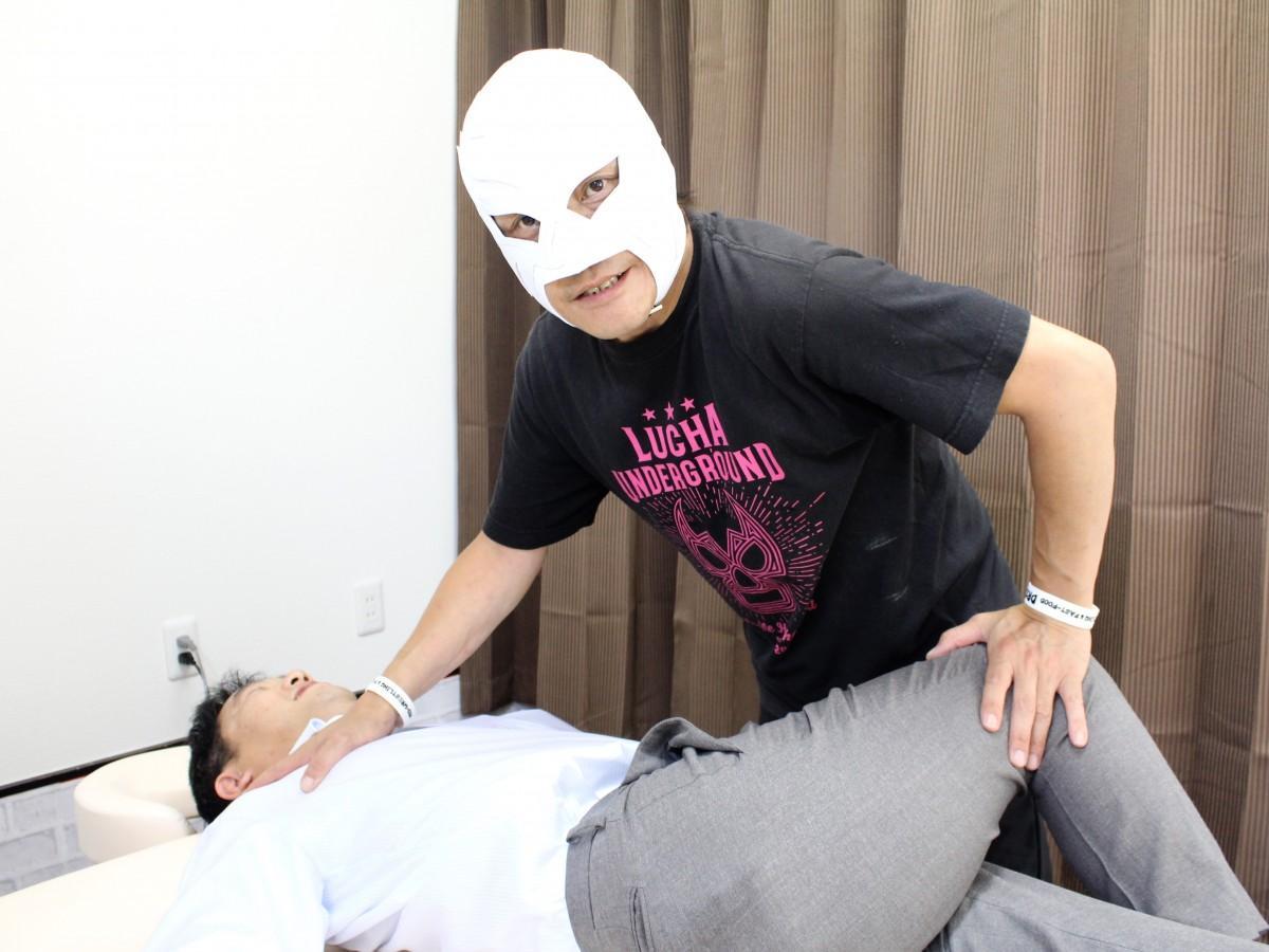 プロレスマスクを着けて施術する平野さん
