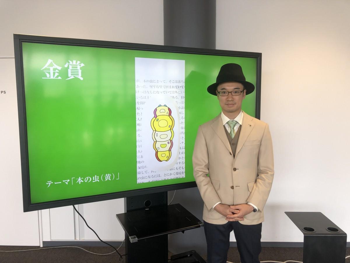 金賞を受賞した山口功さんとその作品「本の虫(黄)」