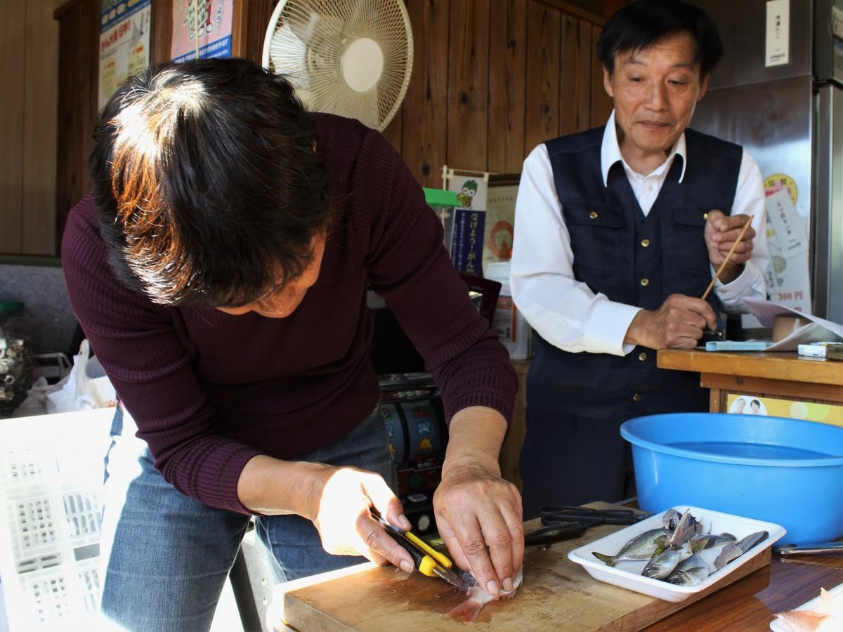 カッターナイフを使った魚の捌き方を教える松岡さん(右)