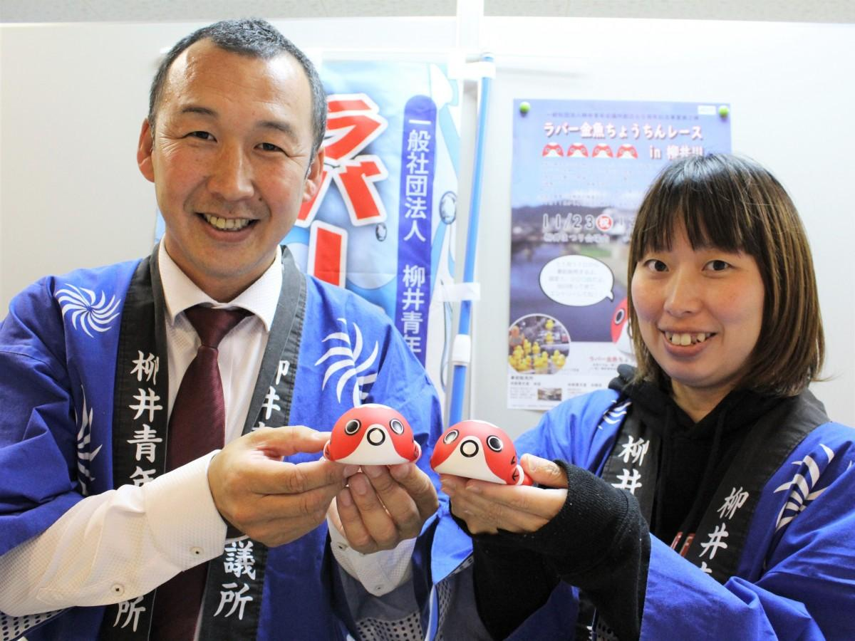 「ラバー金魚ちょうちん」を手に来場を呼び掛ける長井さん(左)