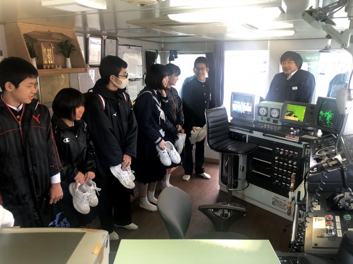 操舵室で船の仕組みを学ぶ中学生