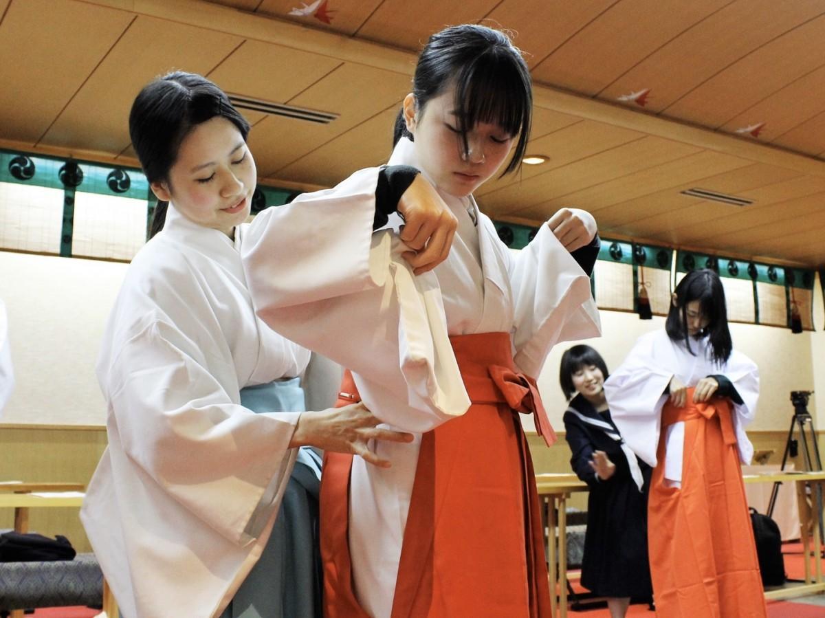 装束の着方を習う学生の巫女