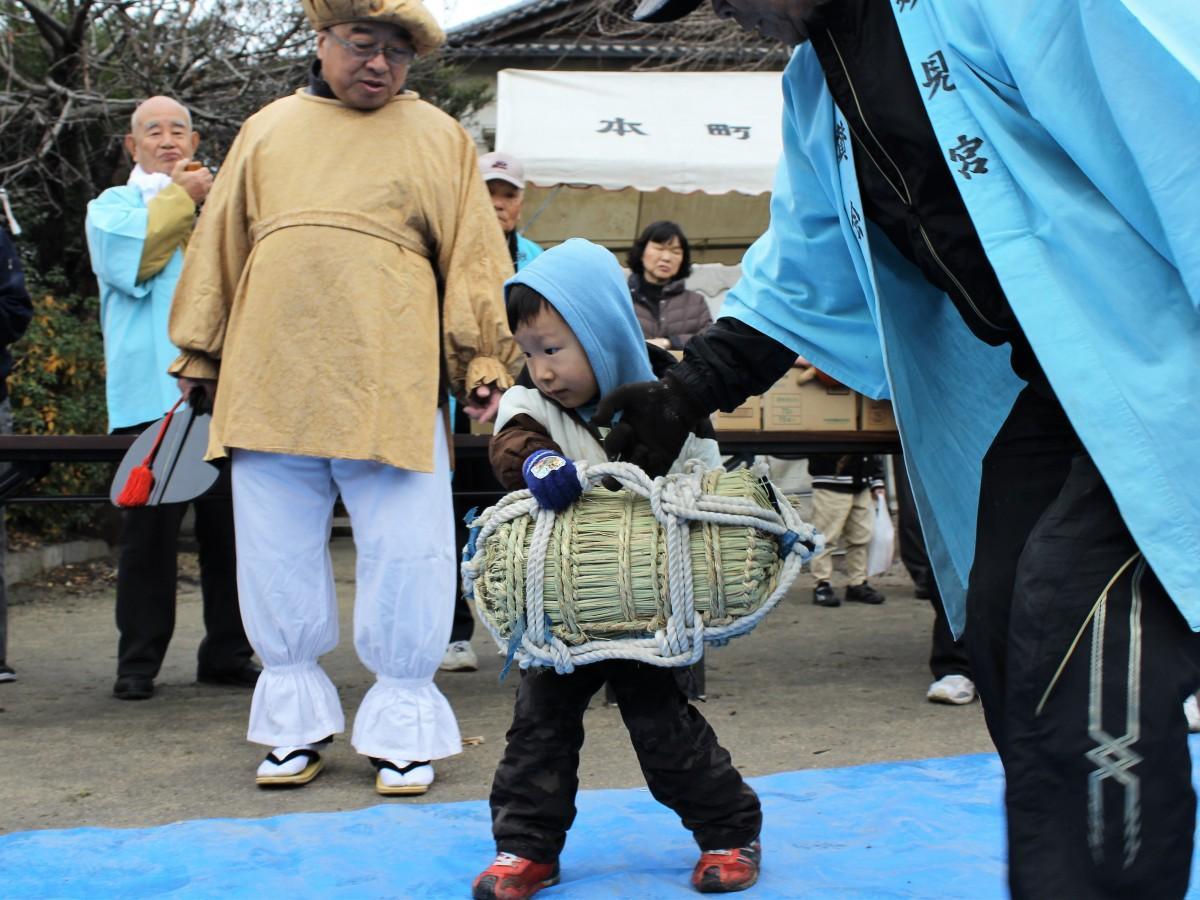 「大黒天」に見守られながら米俵を運ぶ子ども