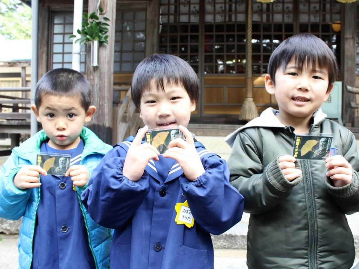 「開運イチョウカード」を手に持つ園児ら