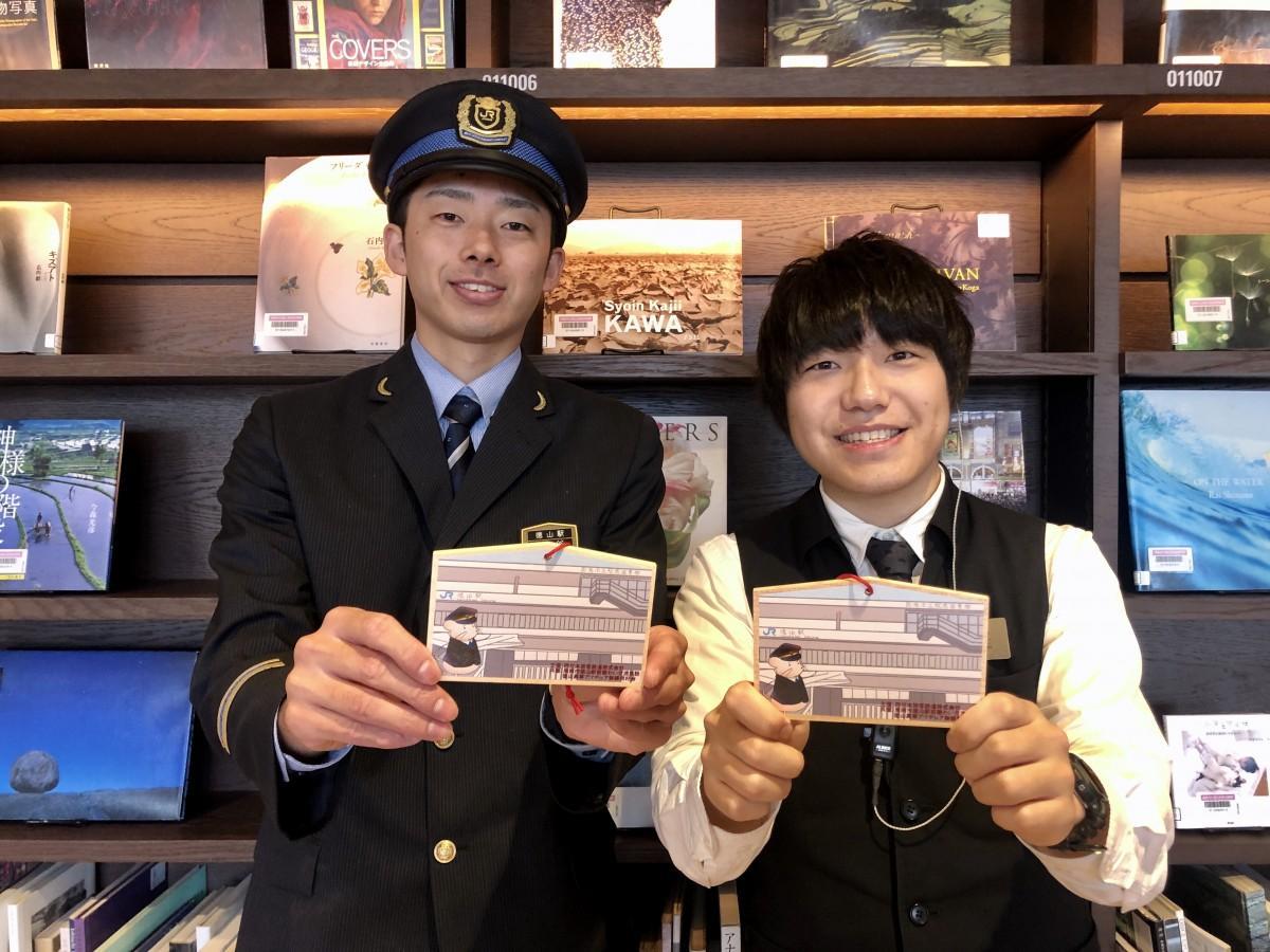 オリジナル絵馬を持つ徳山駅職員と駅前図書館スタッフ