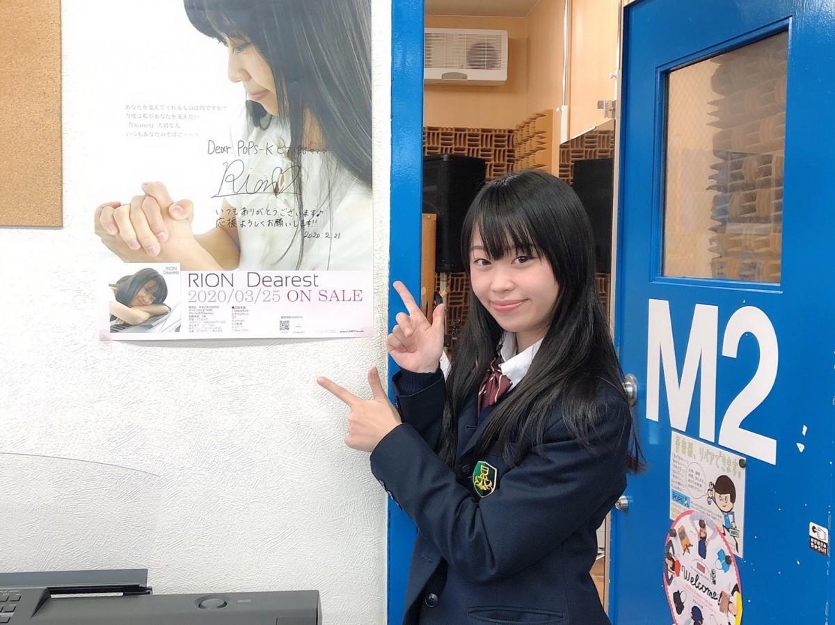 音楽教室にて、サイン入りポスター前でPRするRIONさん