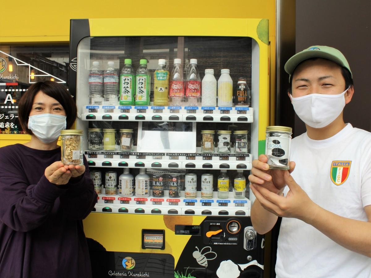 自動販売機の前でPRする藤井さん(右)