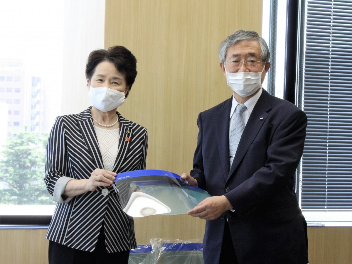 津田会長にフェースシールドを手渡す藤井周南市長