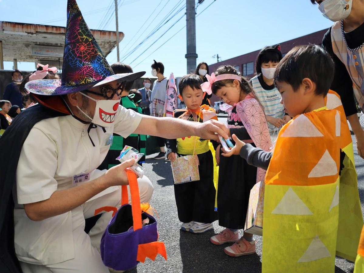 魔法使いに扮した時枝医院長から歯ブラシをもらう園児