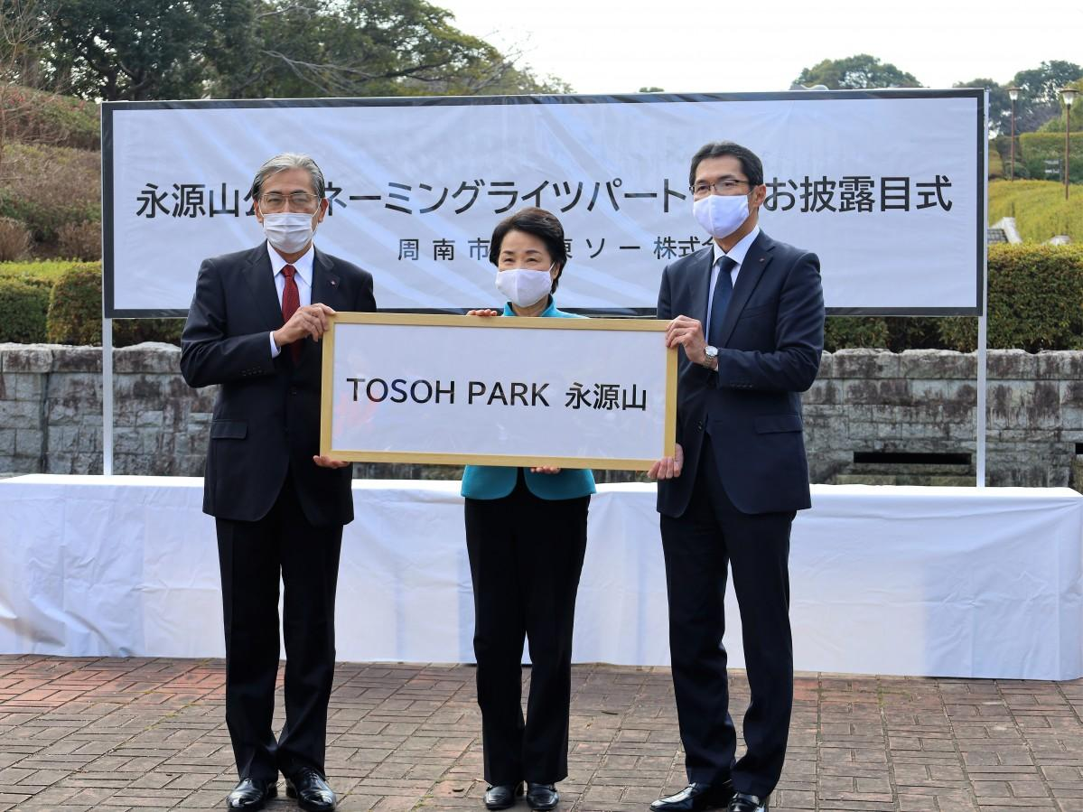 愛称「TOSOH PARK 永源山」を掲げる田代事業所長(左)と藤井周南市長(中央)