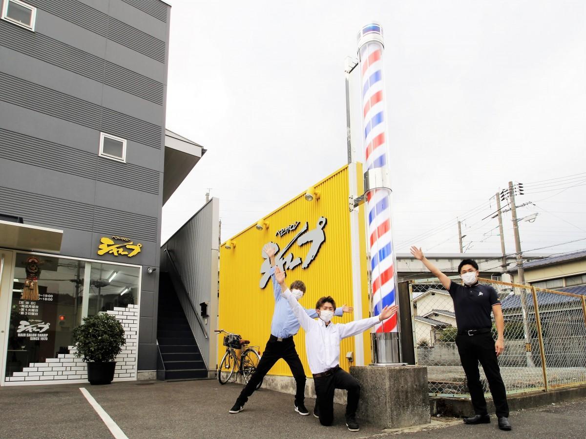 サインポール前で来店を呼び掛けるスタッフと木村さん(右)