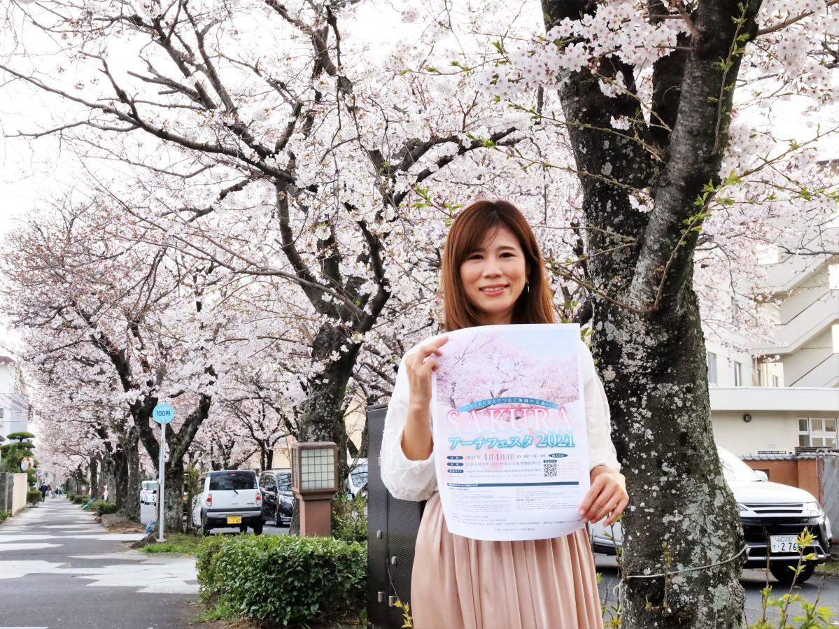会場付近の桜並木でPRする内山さん