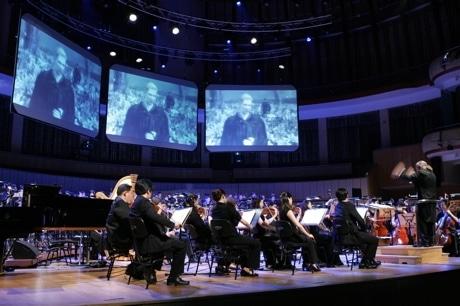 ゲーム画面が映し出されるスクリーンの下で演奏するシンガポール・フェスティバル・オーケストラと指揮のアーニー・ロスさん。