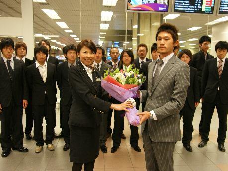 チャンギ空港で日本航空のフライトアテンダントから花束を受け取るアルビレックス新潟・Sの市原充喜選手(写真前列左)
