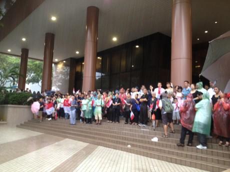 金融庁ビルの前で、故リー・クアンユー初代首相の葬送行列を見送った人々