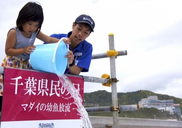 (写真)千葉県の魚「マダイ」の幼魚放流体験をする子どもとサポートをする同園スタッフ