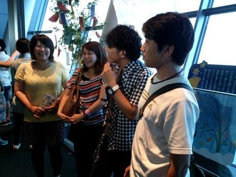 七夕飾りの施された「天望デッキ」で取材陣の質問に応える参加者たち