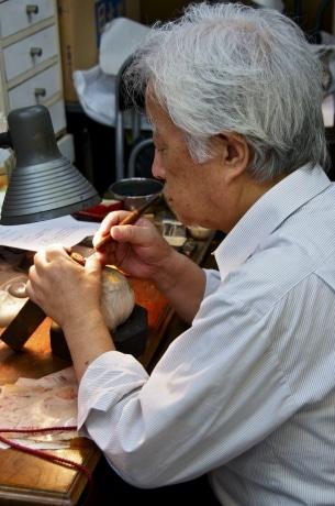 印章を彫る間宮さん。彫るものの材質によって「木口刀」「鉄筆」「ゴム刀」を使い分ける。