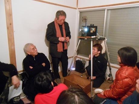 説明をする松本さんと映写機の下で作業をする尼口さん