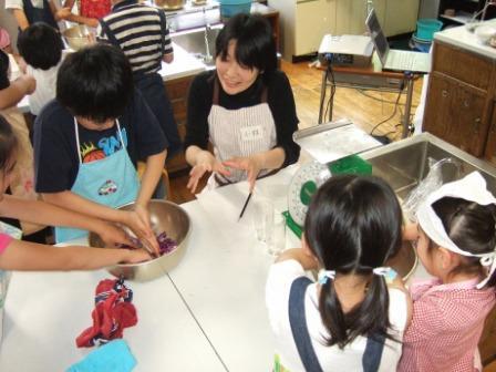 ムラサキキャベツを塩と砂糖で揉みくらべて水分の出る量を調べる実験をする子どもたち