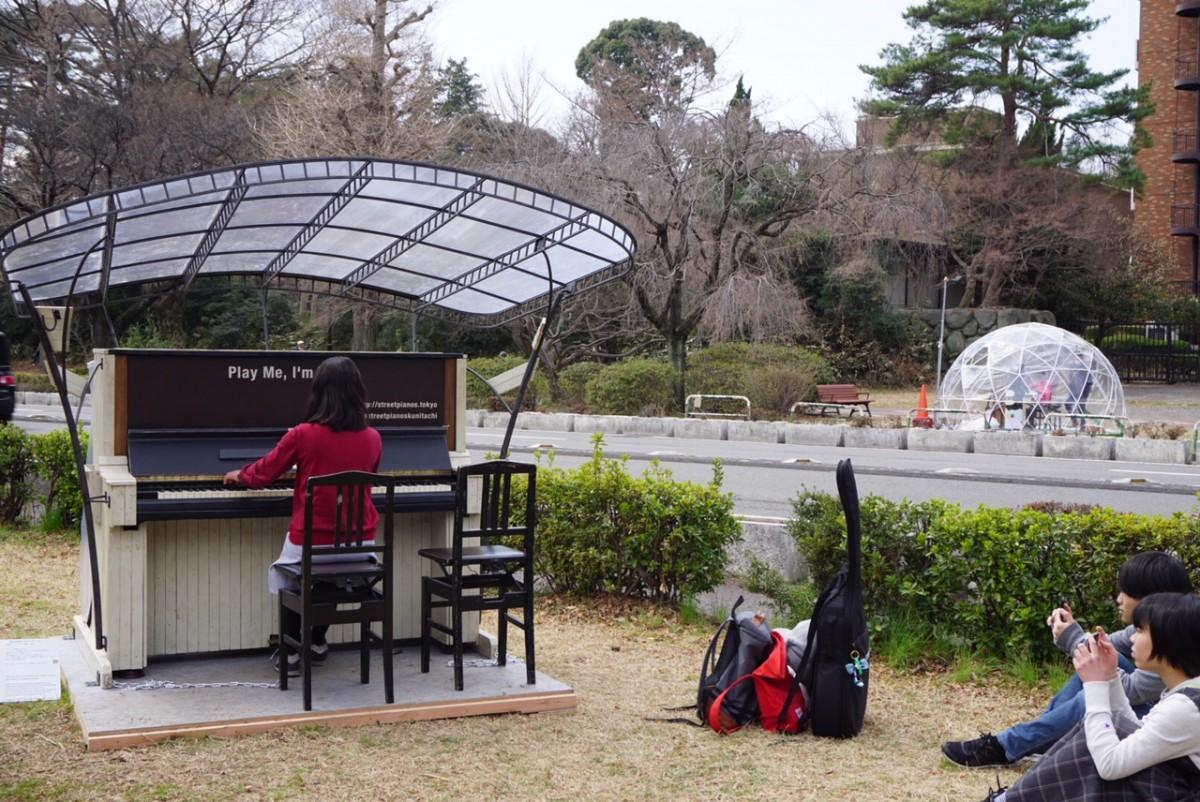 街中でピアノの演奏を楽しむ