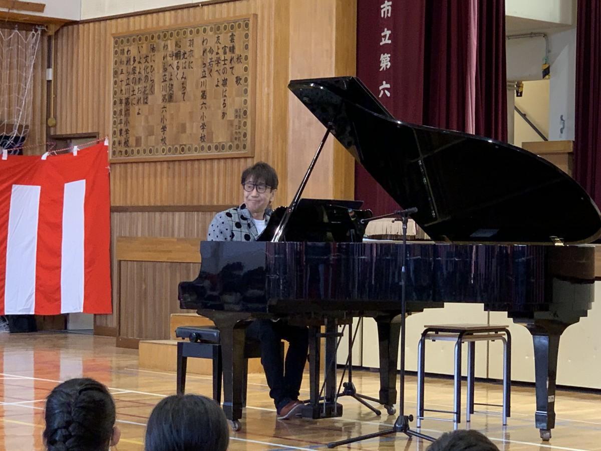 グランドピアノで記念ソングを弾き語りする木根尚登さん